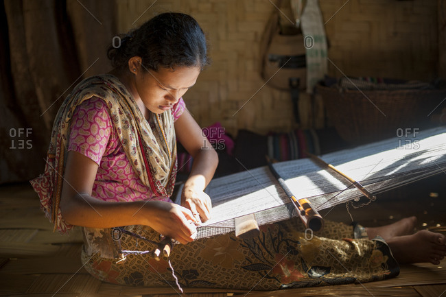A woman weaves using the traditional method on a hand loom