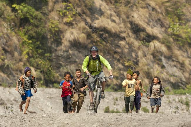 Dobhan, Jagat, Manaslu region, Nepal - February 22, 2012: Children run after a mountain biker along a sandy riverbank in the Manaslu region of Nepal