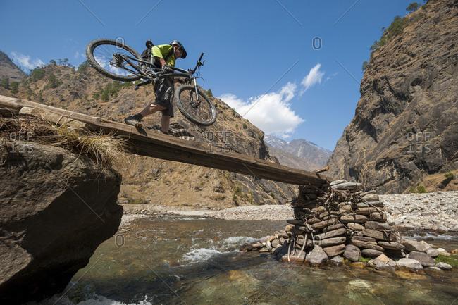 A mountain biker carefully carries his bike  across a narrow bridge