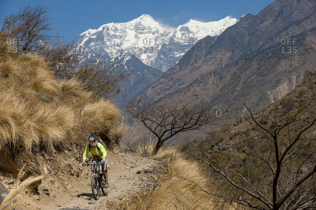 A mountain biker in Nepal with views of Sringi Himal in the distance