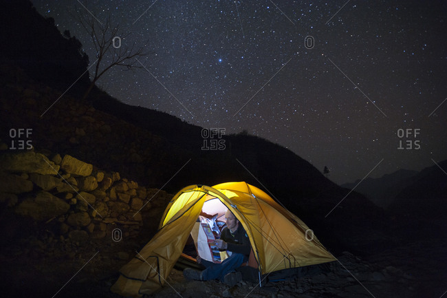A man reads a map by torchlight inside his tent in the Manaslu region