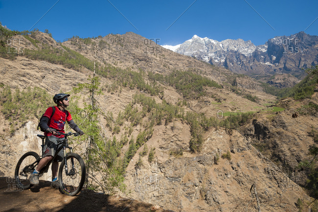 Tsum Valley, Manaslu region, Nepal - February 24, 2012: A mountain biker stops and takes in the view in the Tsum valley in Nepal