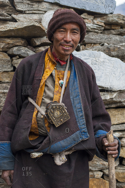 Chule, Tsum Valley, Manaslu region, Nepal - February 24, 2012: A Tibetan man in Tsum valley stands next to a wall of Mani stones