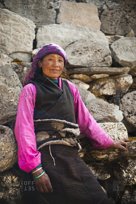 A Tibetan woman in Tsum valley stands next to a wall of Mani stones
