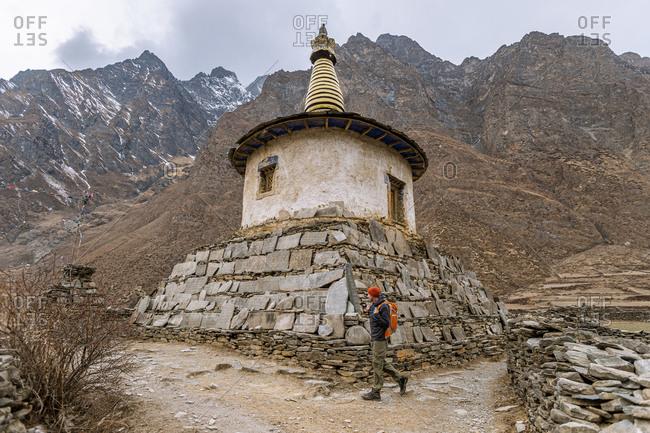 A man trekking in the remote Tsum Valley in the Manslu region of Nepal walks around a Tibetan Stupa