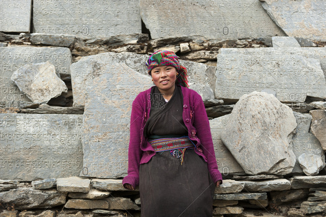 A Tibetan girl in the Tsum valley stands next to a wall of Mani stones