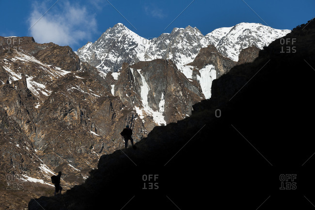 Two trekkers make their way up a steep slope in the Nepal Himalayas
