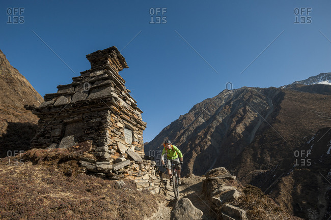 High altitude action as a mountain biker cycles past a Buddhist chorten in the remote Tsum valley in the Nepal Himalaya