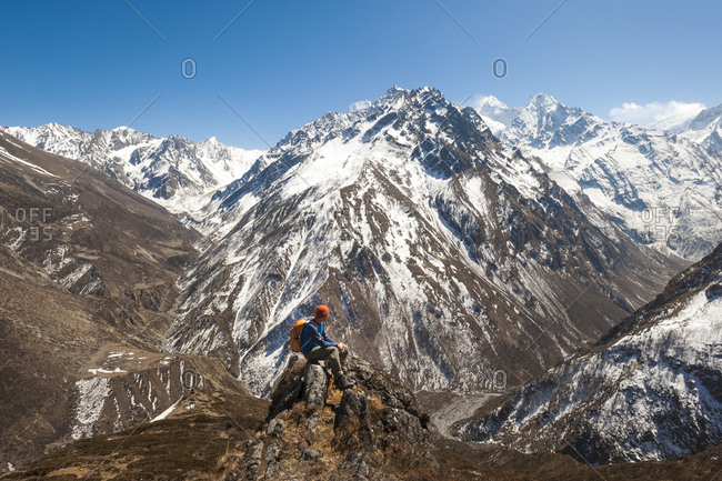 A trekker looks out at the view of Ganesh Himal mountains in Nepal from Mu Gompa at the end of the Tsum valley