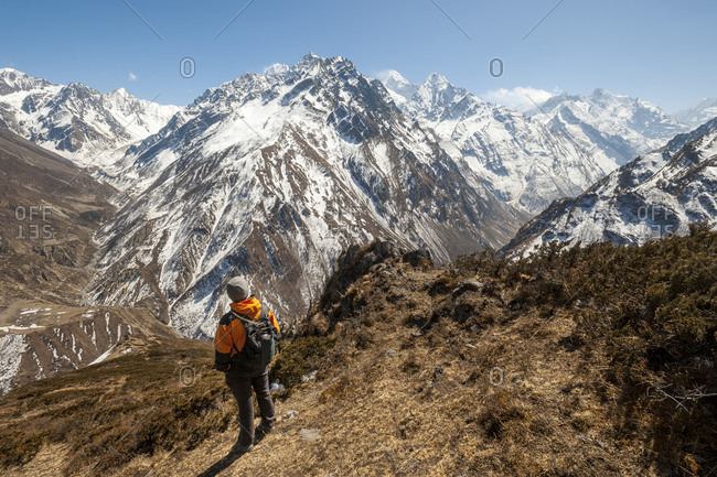 A trekker looks out at the view of Ganesh Himal mountains in Nepal