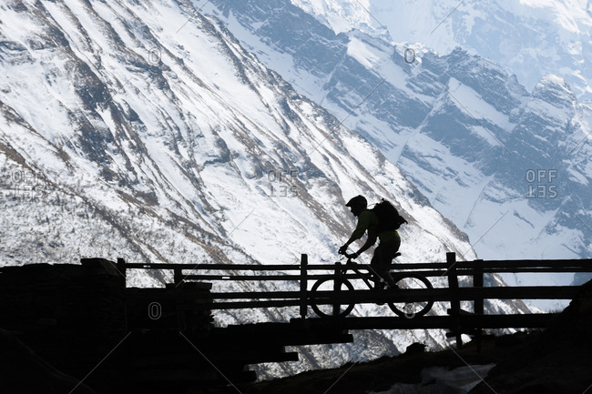 High altitude action as a mountain biker in the remote Himalayan Tsum valley crosses a wooden bridge