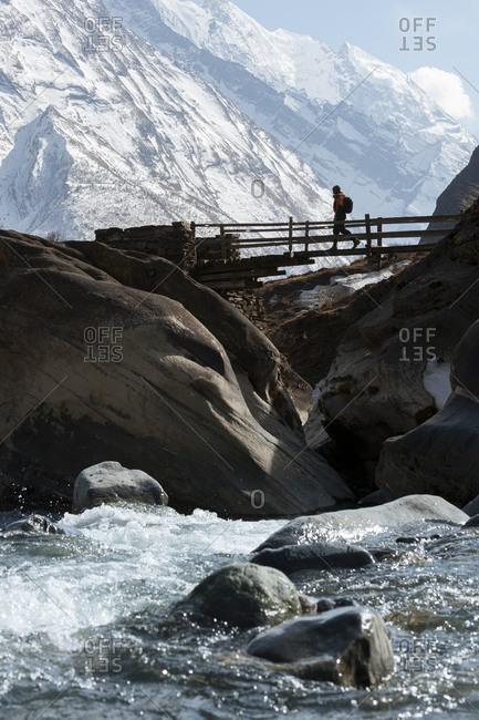 A trekker crosses a wooden bridge in the Tsum valley in Nepal