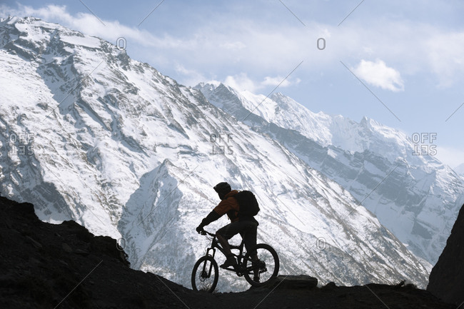 A mountain biker admires the Ganesh Himal in the Tsum valley in Nepal