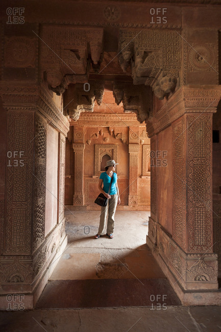 A woman stands in one of archways at Fetehpur Sikri in India