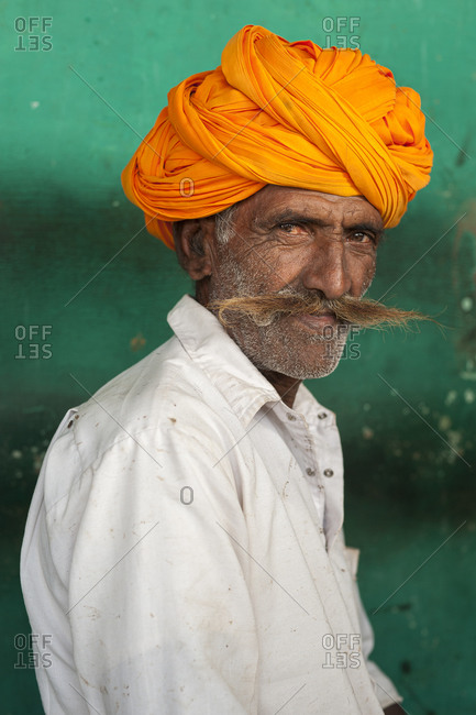A Rajasthani man with a typically large moustache and bright turban sits in a Chai shop near Jodhpur