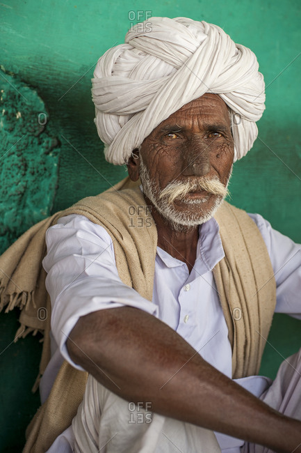An old Rajasthani farmer with a face weathered from years of sun and hard word enjoys a rest in a small chai shop near Bundi in Rajasthan