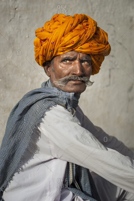 A farmer from Rajasthan with a big moustache wears a brightly colored turban proudly sitting outside his house
