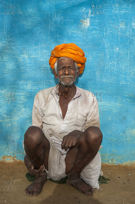 a farmer from Bundi wearing a bright orange turban sitting in front of a vibrant blue painted wall which is a typical sight in Rajastan