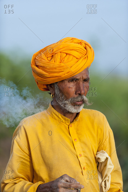 A Rajasthani farmer wearing traditional bright orange clothes and turban