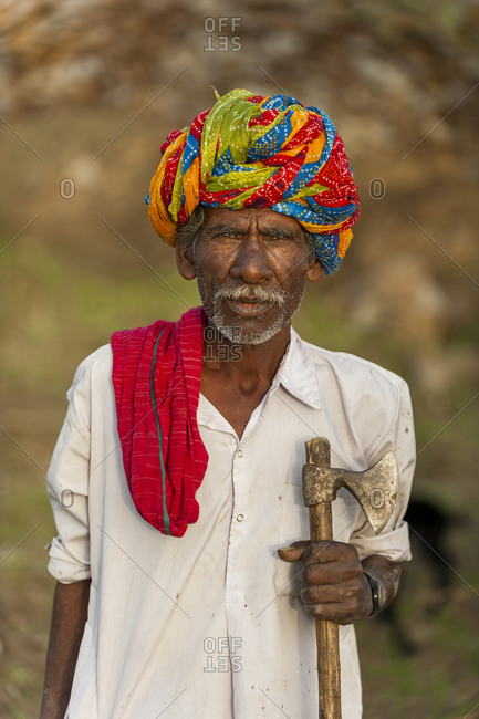 A farmer wearing traditionally brightly colored turban in the dry state of Rajasthan in India