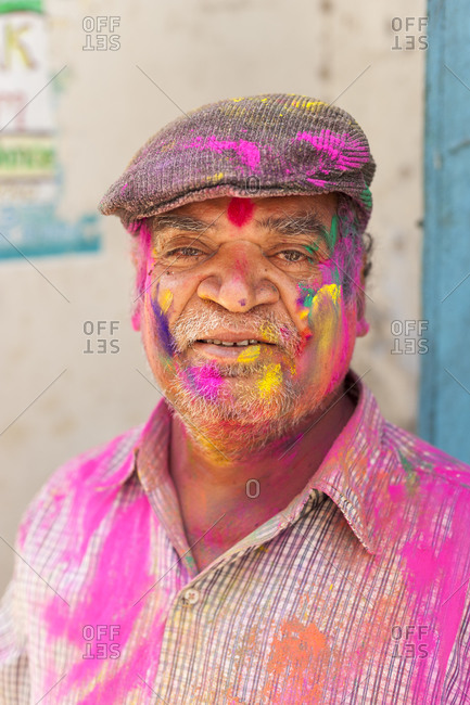 Udaipur, Rajasthan, India - March 8, 2012: A man is happily covered in colorful powder during the festival of color in Rajasthan