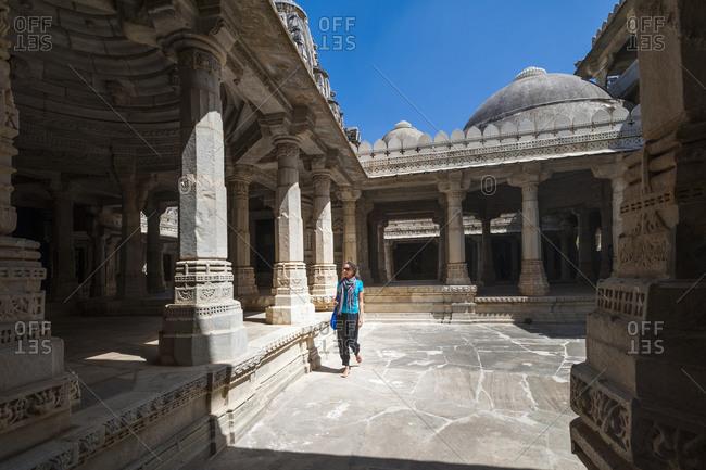 A tourist admires the intricate marble pillars at Ranakpur Jain Temple