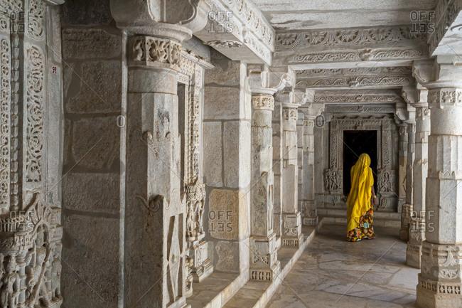Ranakpur Temple, Rajasthan, India - March 9, 2012: A Hindu woman wearing traditional Sari vistis Ranakpur Jain temple