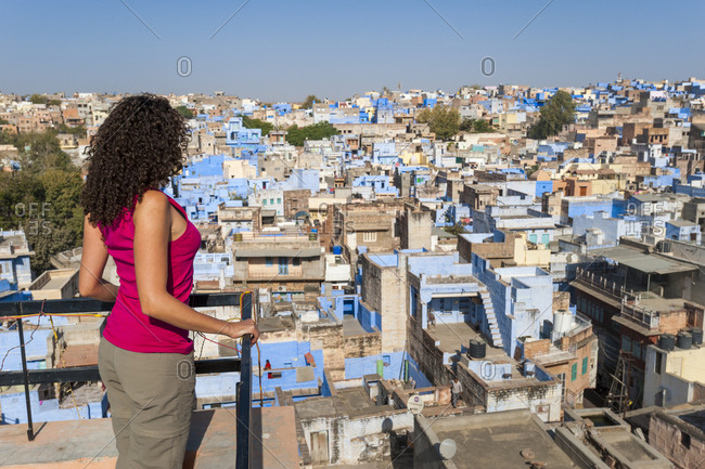 A tourist looks out over rooftops of the famous blue buildings of Jodhpur
