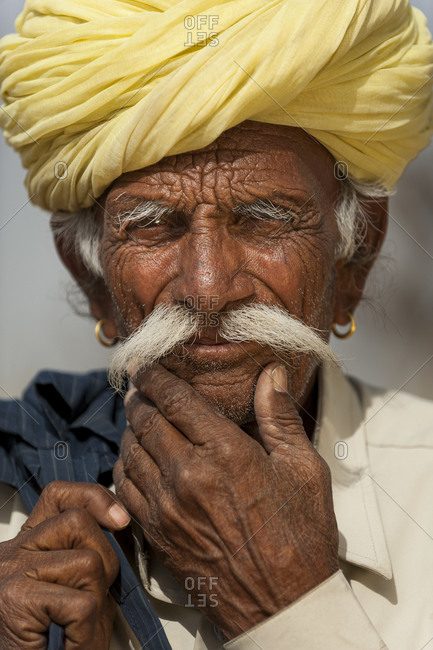 A ageing Rajasthani man wearing traditional turban and ear rings
