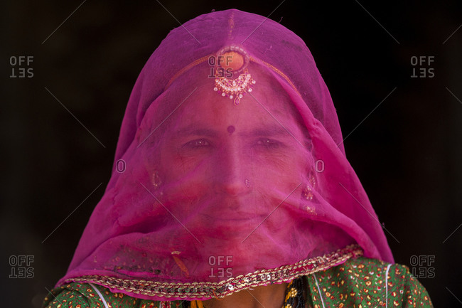 A Rajasthani woman wearing traditional jewelry and a veil called a Ghoonghat