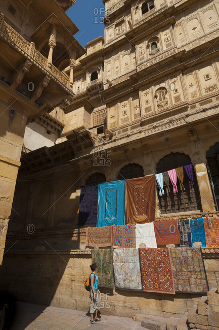 A tourist stops to look at carpets hanging in Jaisalmer Fort in Rajasthan