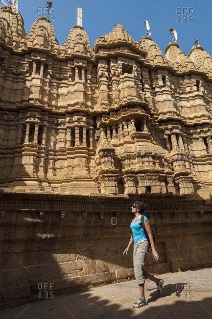 A tourist walks past a Jain Temple within Jaisalmer Fort