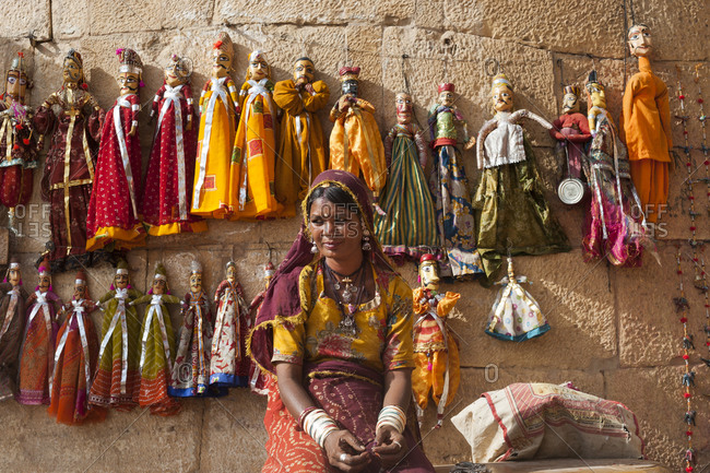 Jodhpur district, Rajasthan, India - March 14, 2012: A woman sells puppets along the fort walls in Jaisalmer in the desert of Rajasthan