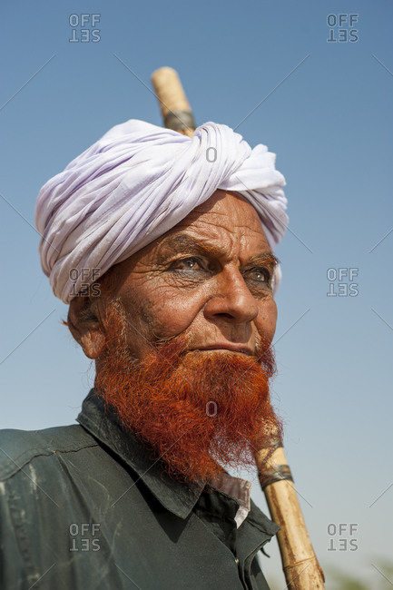 A Muslim man with a beard and eyebrows dyed in henna and wearing black khol under the eyes which is an ancient eye cosmetic made by grinding lead sulfide