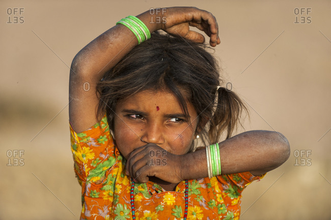 A little Rajasthani girl shyly looks to one side to avoid the camera