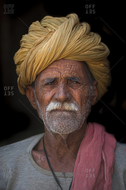 A Rajasthani man wearing a turban sits in the doorway of his house