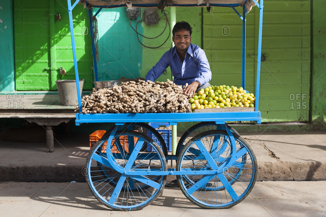 Nawalgarh, Shekawati, Rajasthan, India - March 16, 2012: A man sits on a push cart stall selling ginger and lemons
