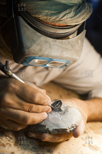A worker carefully exposes a Trilobite from the surrounding rock