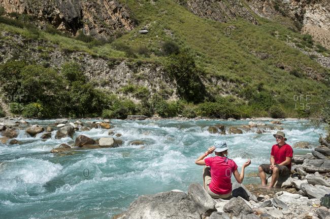Hikers take a break beside a river in Dolpa, a remote region of Nepal
