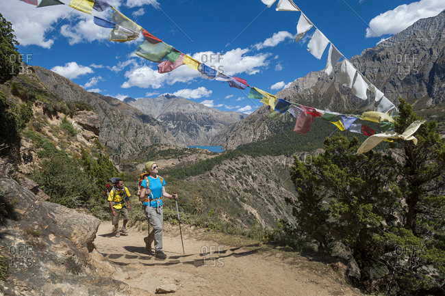 Prayer flags mark a high point in the trail with a view of Phoksundo lake far off in the distance in Dolpa, a remote region of Nepal