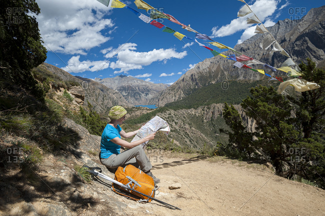 Stopping beside the trail to check the map with a view of Phoksundo lake far off in the distance in Dolpa, a remote region of Nepal