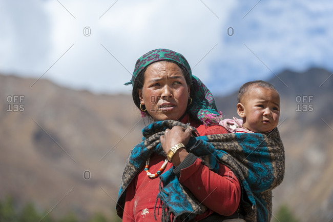 A Tibetan woman carrying her baby in a shawl on her back in Dolpa, a remote region of Nepal