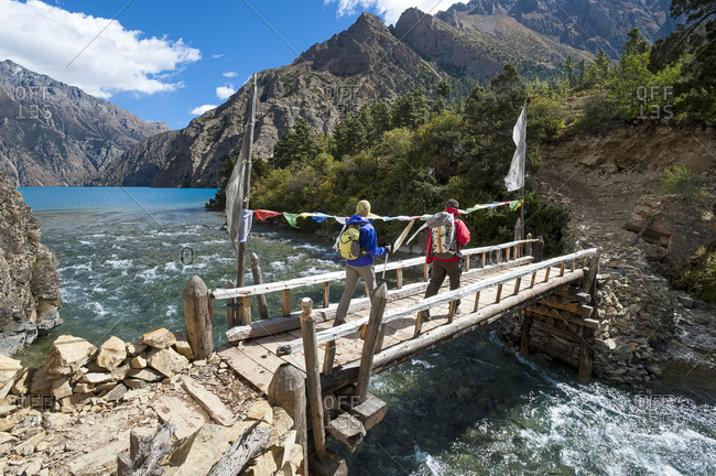 A couple of hikers admire the spectacular blue of Phoksundo lake while crossing a bridge in Dolpa, a remote region of Nepal