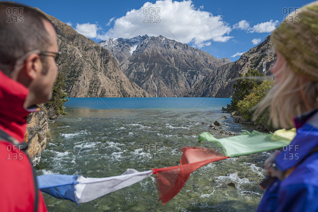 A couple of hikers stop to admire the spectacular blue of Phoksundo lake in Dolpa, a remote region of Nepal