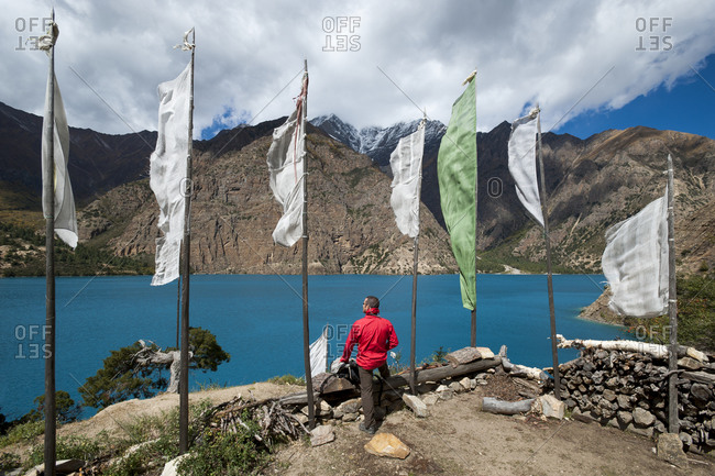 A hiker stops to look out over Phoksundo lake in Dolpa, a remote region of Nepal