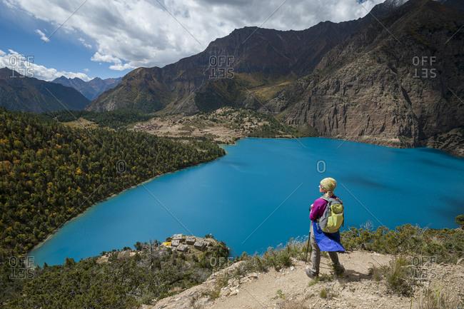 A trekker stands above the turquoise blue Phoksundo lake in the Dolpa region of Nepal