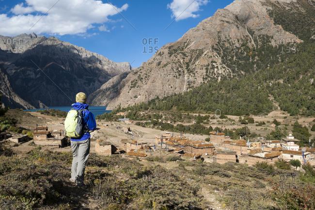 A trekker looks down on the old Tibetan settlement of Ringmo and the turquoise blue Phoksundo lake in the Dolpa region of Nepal