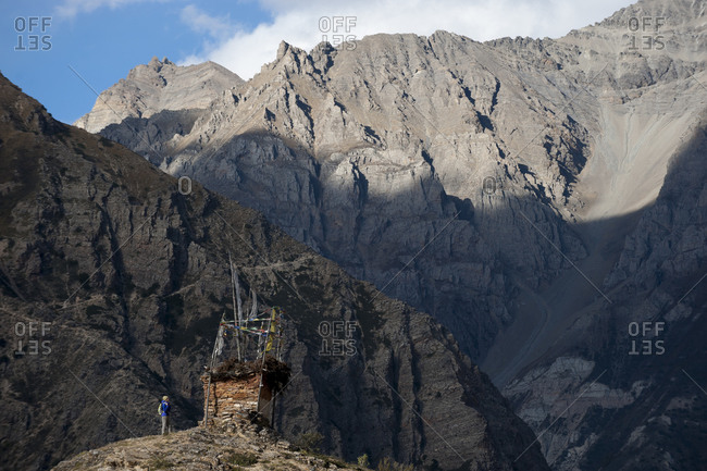 An old Tibetan chorten strewn with prayer flags marks the top of a hill near Ringmo in Dolpa. The trail leading to Shey Gompa can be seen in the side of the rock face in the distance