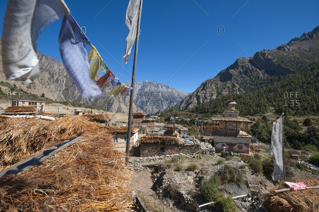 Prayer flags and rooftops in the little village of Ringmo near Phoksundo lake in Dolpa which is a remote region of Nepal