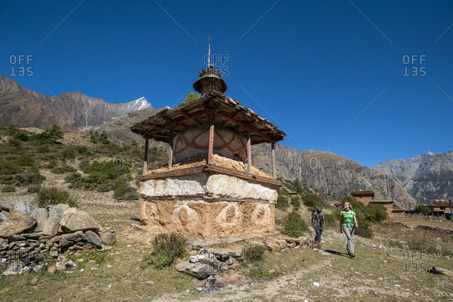 Trekkers pass a Tibetan chorten beside the trail near Ringmo in Dolpa, a remote region of Nepal